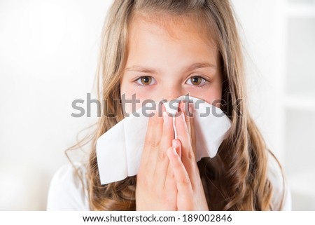 A beautiful young blond girl is sneezing in her tissue because of her cold - stock photo