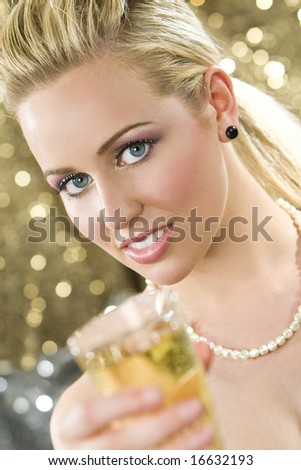 A beautiful young blond haired, blue eyed woman enjoying a glass of champagne