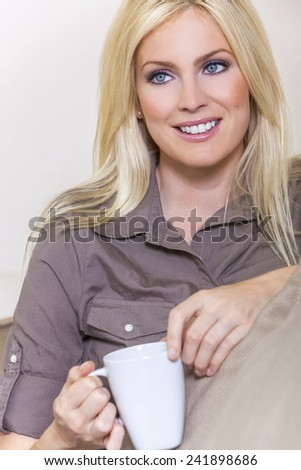 A beautiful young blond woman drinking tea or coffee from a white mug sitting at home on a her sofa - stock photo