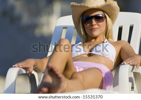 A beautiful young blond woman in sunglasses and cowboy hat relaxes in the sun by the sea - stock photo