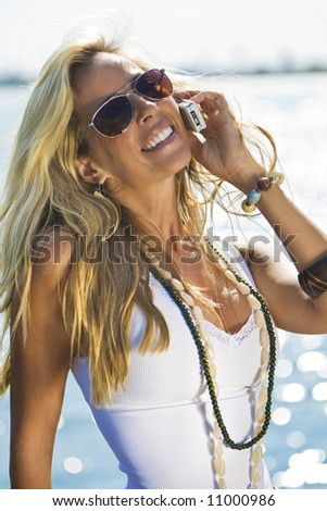 A beautiful young blond woman on the phone with the sun reflecting off the sea behind her - stock photo