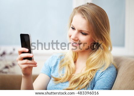 A beautiful young blond woman smiling sitting on a sofa looking at her smart phone.