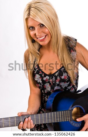 A beautiful young, blonde, female playing a blue guitar in a floral print dress. - stock photo