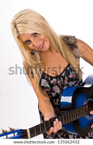 A beautiful young, blonde, female playing a blue guitar in a floral print dress.