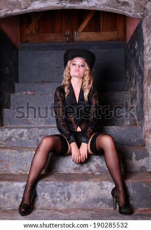 A beautiful young blonde lady is posing in an old pub and restaurant. She is wearing various Broadway performer outfits. Black lingerie and cowboy hat. - stock photo