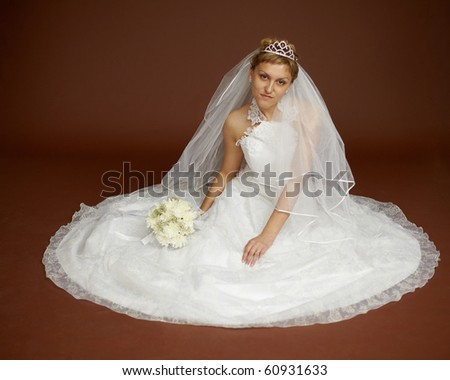 A beautiful young bride in a white dress on a brown background - stock photo