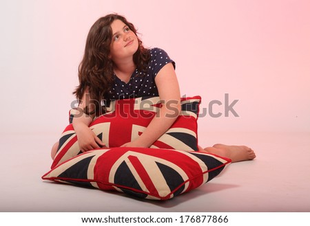 A beautiful young brunette girl is hugging her pillow with the union jack colors on it. - stock photo