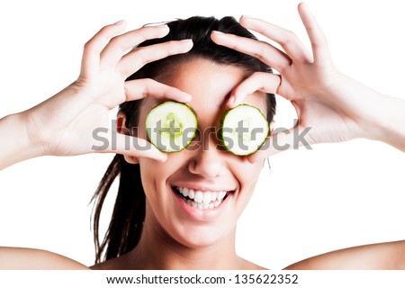 a beautiful young caucasian girl with dark brunette hair holding two slices of cucumber delicately in front of her eyes smiling brightly showing off her dimples - stock photo