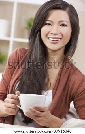 A beautiful young Chinese Asian Oriental woman with a wonderful toothy smile drinking tea or coffee from a white cup and saucer - stock photo