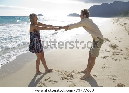 A beautiful young couple play around on the beach in Hawaii - stock photo