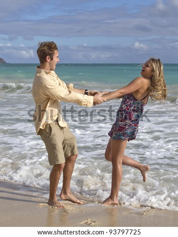 A beautiful young couple swing in each others arms on the beach in Hawaii - stock photo