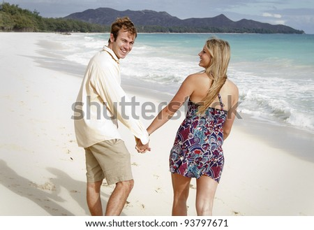 A beautiful young couple walks on the beach in Hawaii - stock photo