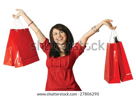 A beautiful young female holding shopping bags with a huge grin on her face. - stock photo
