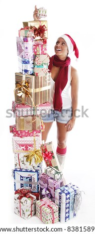A beautiful young female piling Christmas gifts, putting the top gift