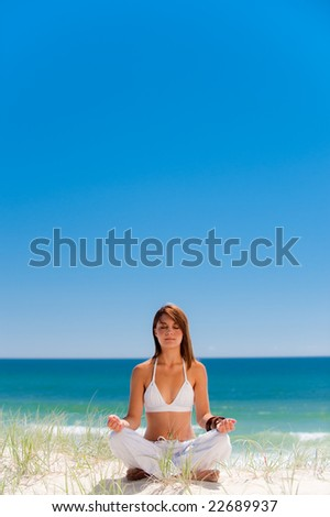 A beautiful young girl doing yoga on an empty beach - stock photo