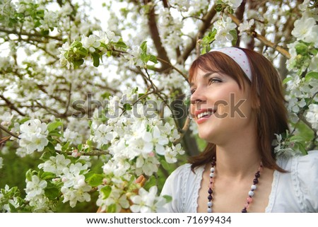 A beautiful young girl dressed in white on a background of apple blossoms