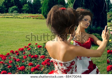 a beautiful young girl in a red dress look in the mirror