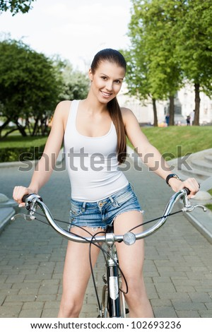 A beautiful young girl in a white T-shirt and blue jeans is riding a bicycle through the city - Outdoors - stock photo