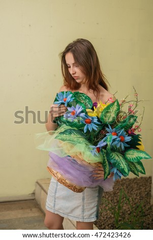 A beautiful young girl is standing next to a colorful bouquet