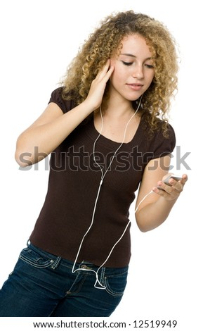 A beautiful young girl listening to music on her mp3 player - stock photo