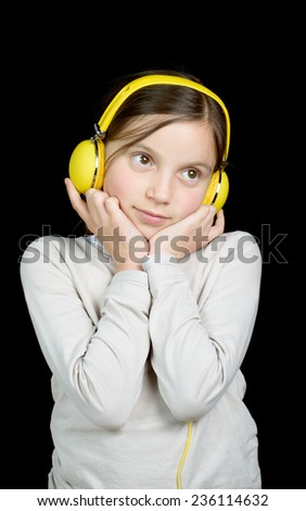 a beautiful young girl listening to music with headphones - stock photo
