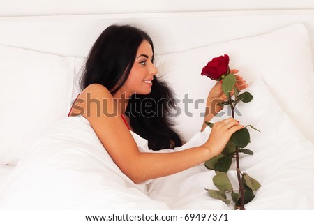 A beautiful young girl lying in bed with gifts, roses, woke up, asleep. - stock photo