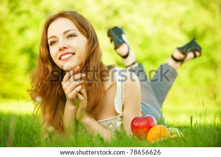 A beautiful young girl lying on the grass beside a basket of fruit is, on a background of green nature - stock photo