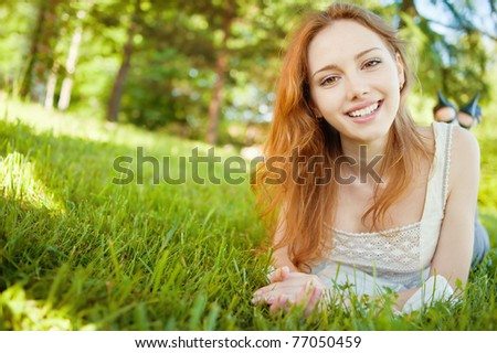 A beautiful young girl lying on the grass on a background of green nature - stock photo