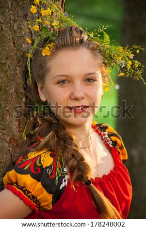 A beautiful young girl standing by the tree