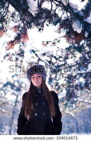 a beautiful young girl standing in the middle of the winter woods - stock photo