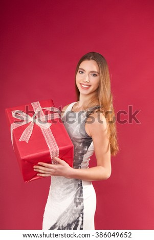 a beautiful young girl with a box wrapped in gift paper in hands on red background