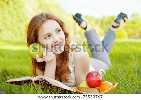 A beautiful young girl with an apple lying on the grass and reading a book beside a basket of fruit is, on a background of green nature - stock photo