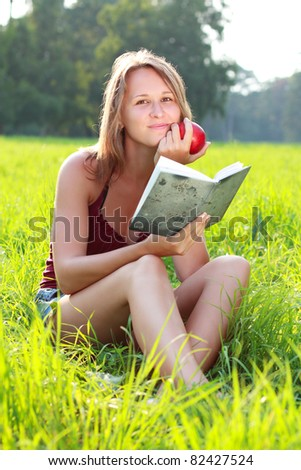 A beautiful young girl with an apple sitting on the grass and reading a book on a background of green nature