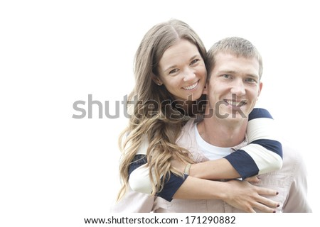 A beautiful young happy caucasian couple posing with the beach in the background on a cloudy day. - stock photo