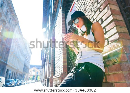A beautiful young Hip Hop Rapper girl with Headphones in a urban environment. - stock photo