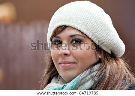A beautiful young Hispanic woman with a smile on her face wearing a winter buret style knit hat. - stock photo