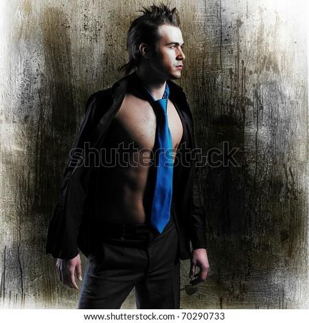 A beautiful young man posing on grunge background. Fashion photo - stock photo
