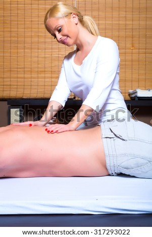 A beautiful young masseuse applying a massage to a male client in a studio.  - stock photo