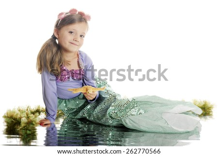 A beautiful young mermaid happily holding a starfish at the water's edge, surrounded by seaweed.  On a white background.