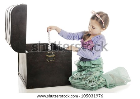 A beautiful young mermaid pulling a strand of large pearls from an old treasure chest.  On a white background. - stock photo