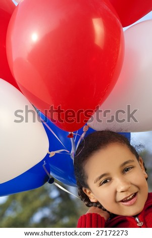 A beautiful young mixed race girl looking very happy with her big bunch of red, white and blue balloons - stock photo