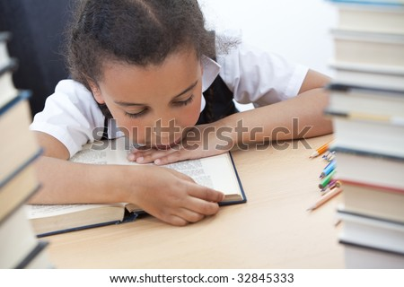 A beautiful young mixed race girl reading in a school classroom with a pile of books in front of her - stock photo