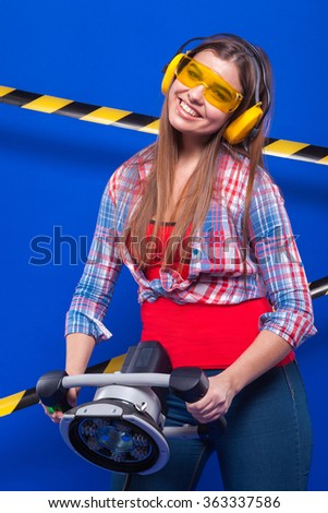 a beautiful young model plus size standing on a blue background with a black and yellow ribbon fencing construction headphones and protective yellow sunglasses and holding an electric sander  - stock photo