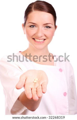A beautiful young nurse offering pills and smiling to the camera. Focus is on the pills in the foreground.