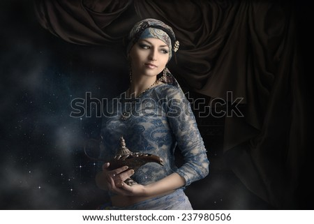 A beautiful young oriental woman with a lamp on a black background