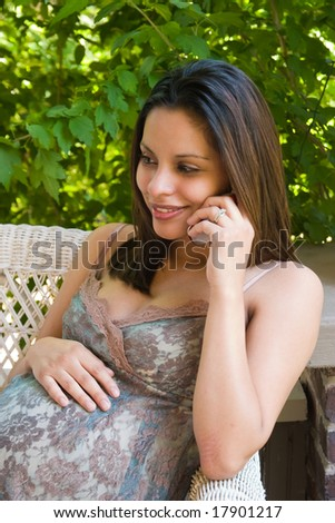 A beautiful young pregnant Hispanic woman talking on a cellphone and relaxing outside white waiting for the birth of her baby. - stock photo