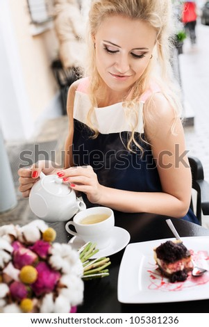 A beautiful young woman are pouring tea. Holding a cup of tea. Outdoors - stock photo