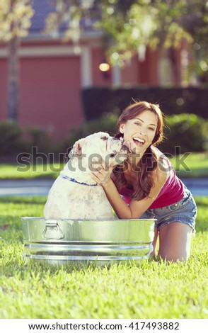 A beautiful young woman being licked by her pet dog, a bulldog, while washing him outside in a metal tub