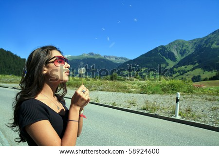 A beautiful young woman blowing a dandelion on the side of the road in the Engadin region of the Swiss Alps. - stock photo
