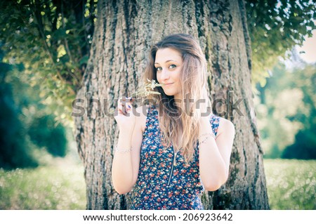 A beautiful young woman close to a tree in a park, in a warm vintage-like sunset light. - stock photo